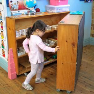Beverly Montessori girl looking for toys