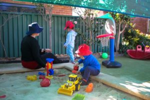 Beverly Montessori teacher and kids in sandbox